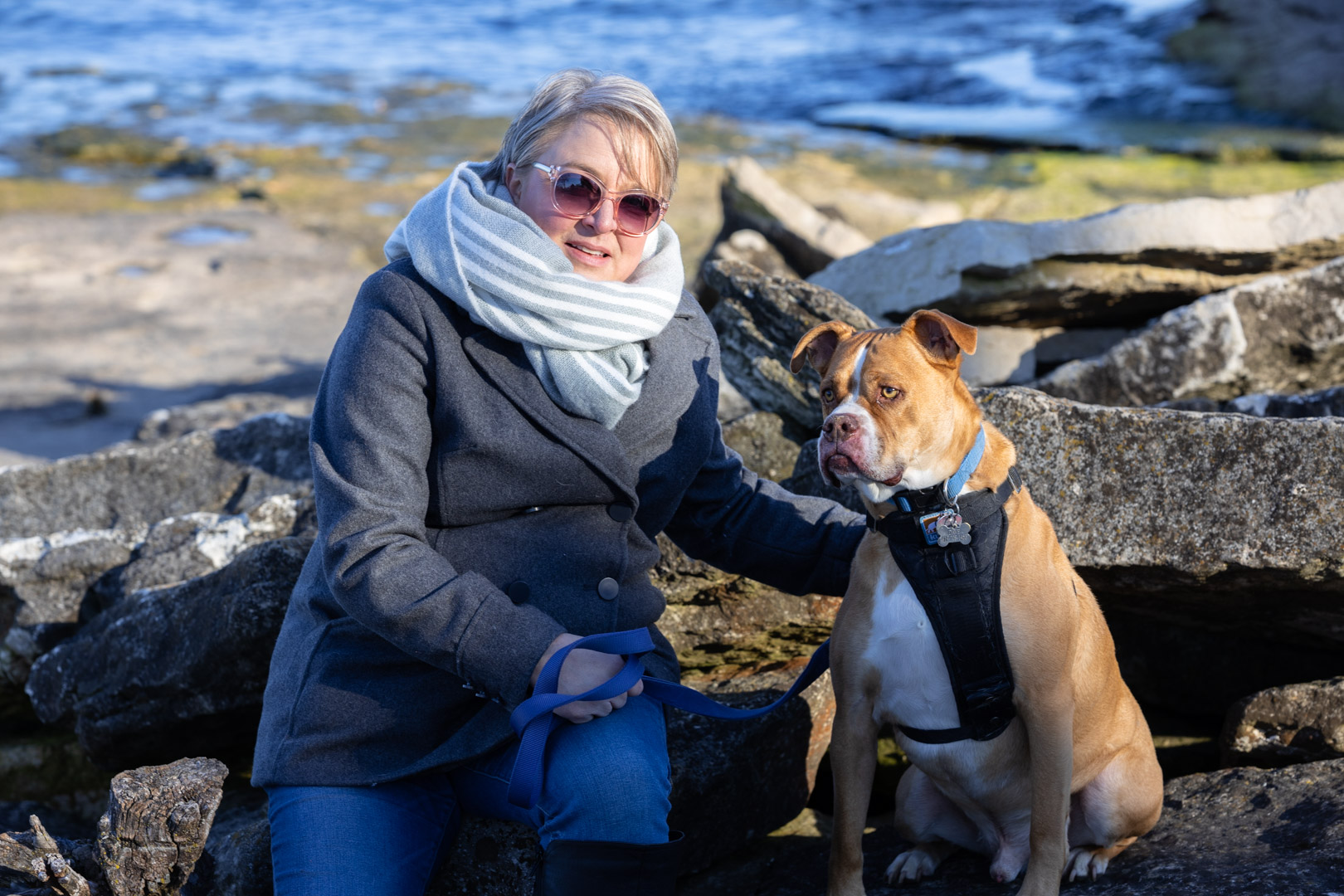 Woman and her boxer posing on the rocks at Marblehead Light House